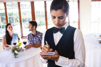 waitress-writing-order-on-notepad-in-restaurant-5CTVN5E